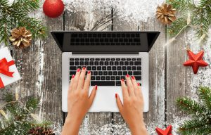 Woman work on laptop computer. Blank display for mockup. Christmas tree with decorations, and gift beside.